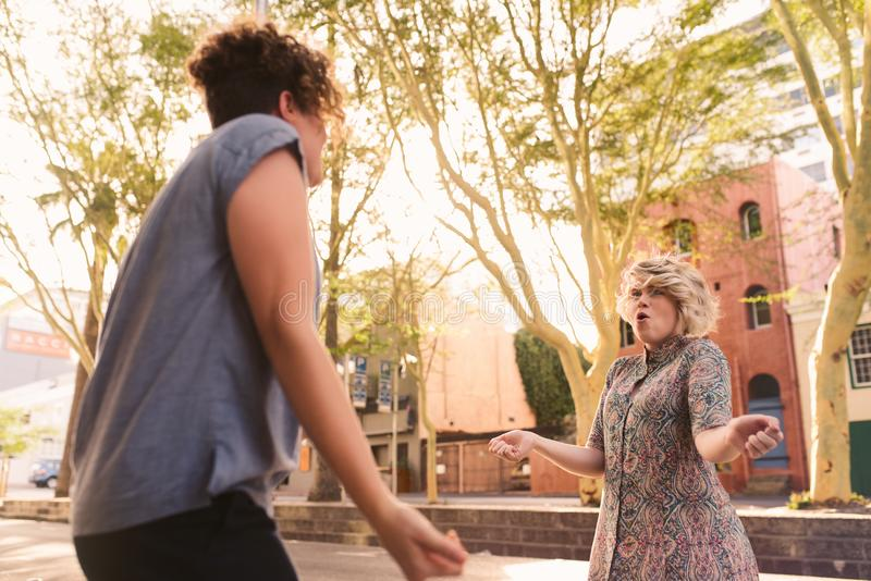 Giovani coppie lesbiche spensierate che ballano insieme su una via della città immagine stock