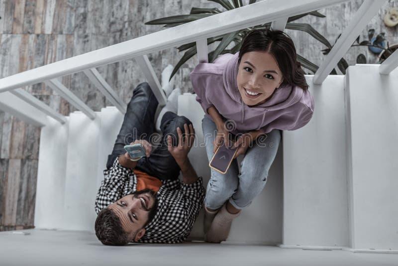 Giovani coppie moderne che comperano online facendo uso dei loro telefoni fotografia stock