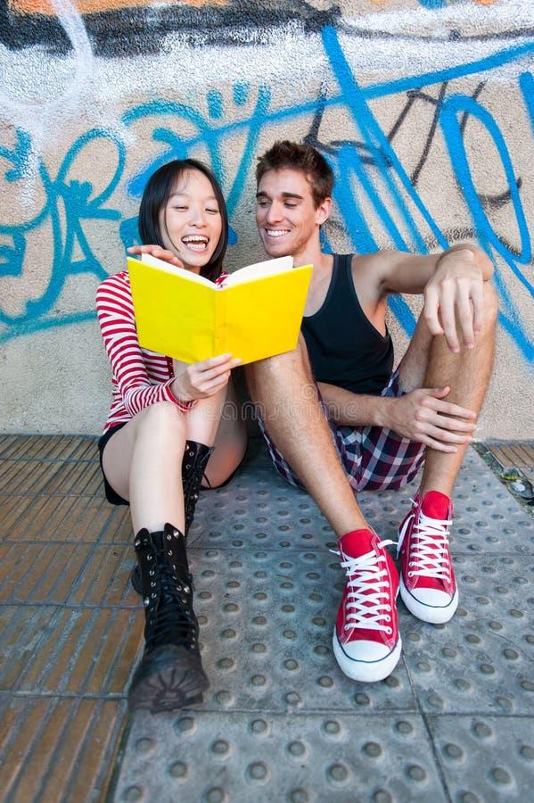 Giovani coppie multi-etniche che leggono un libro immagini stock