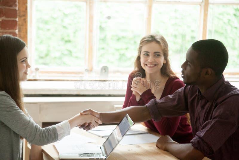 Giovani coppie multietniche che stringono le mani con l'agente immobiliare immagini stock libere da diritti