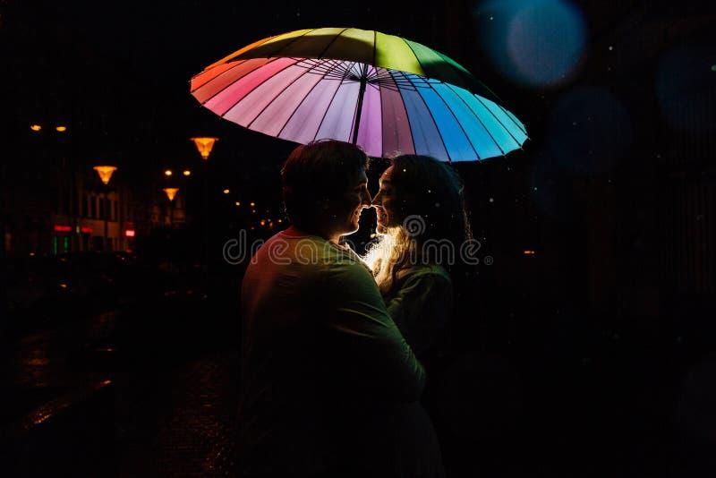 Giovani coppie nell'ambito dei baci di un ombrello alla notte su una via della città fotografia stock