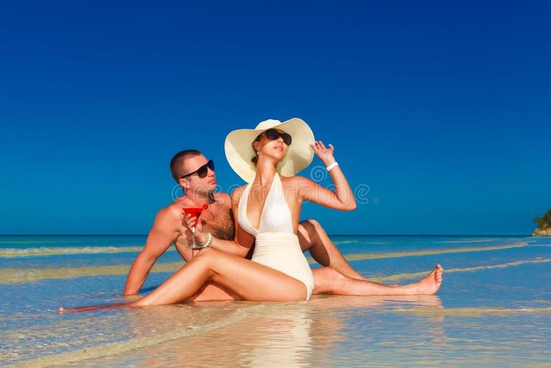 Giovani coppie nell'amore alla spiaggia ed al cocktail tropicali godere immagine stock