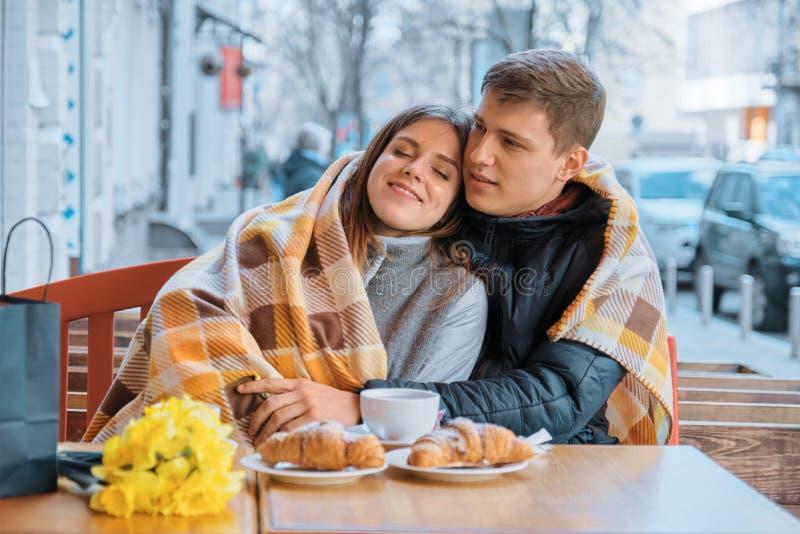 Giovani coppie nell'amore in caffè all'aperto sotto il plaid, mazzo giallo sulla tavola, caffè, croissant della molla fotografie stock libere da diritti