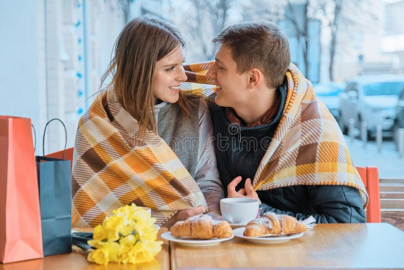 Giovani coppie nell'amore in caff? all'aperto sotto il plaid, mazzo giallo sulla tavola, caff?, croissant della molla immagini stock
