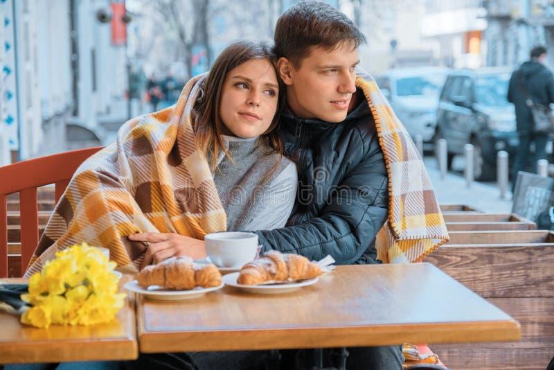 Giovani coppie nell'amore in caff? all'aperto sotto il plaid, mazzo giallo sulla tavola, caff?, croissant della molla immagine stock libera da diritti