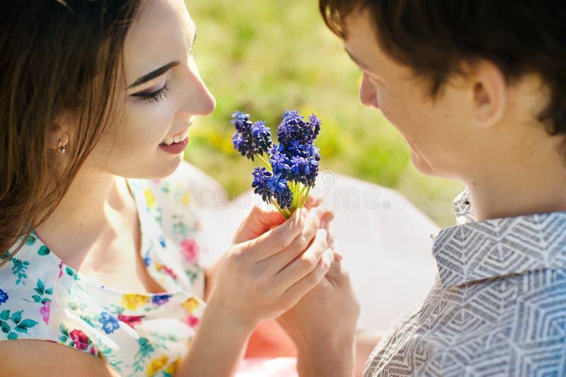 Giovani coppie nell'amore che bacia e che abbraccia ai fiori blu Fine in su fotografie stock libere da diritti