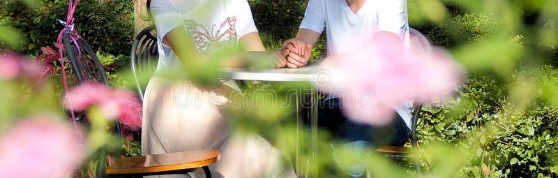 Giovani coppie nell'amore che bacia e che abbraccia al parco nel giorno soleggiato immagini stock