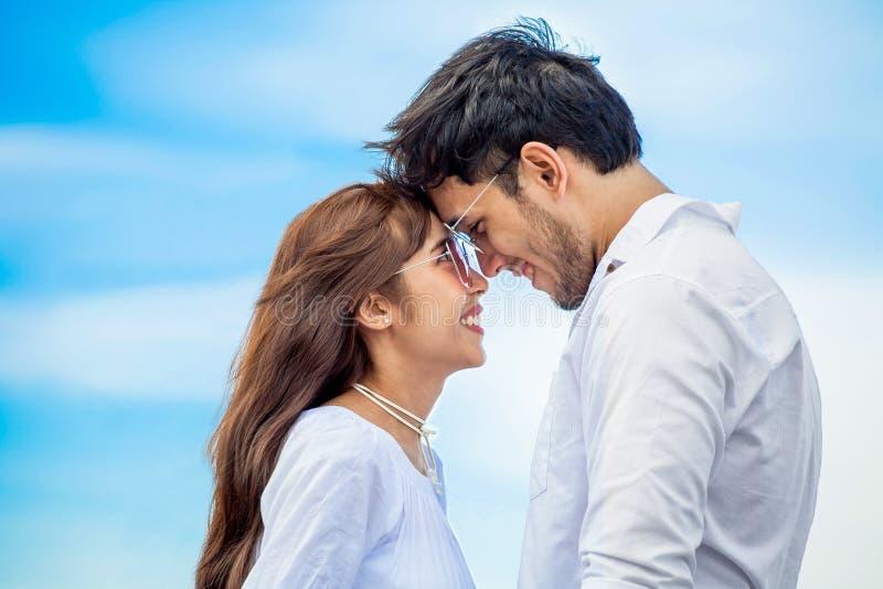 Giovani coppie nell'amore che guarda l'un l'altro e che tiene insieme mano alla spiaggia del mare su cielo blu giovani nozze sorr fotografie stock libere da diritti
