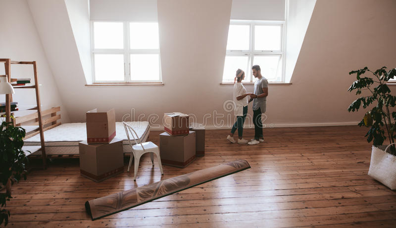 Giovani coppie nell'amore che si muove in un nuovo appartamento immagini stock libere da diritti