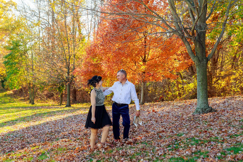 Giovani coppie nell'amore che si tiene per mano e che cammina attraverso un parco il giorno soleggiato di autunno fotografia stock