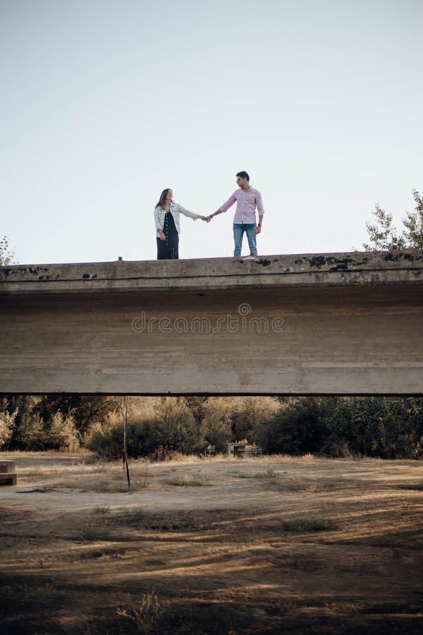 Giovani coppie nell'amore che si tiene per mano su un vecchio ponte immagini stock