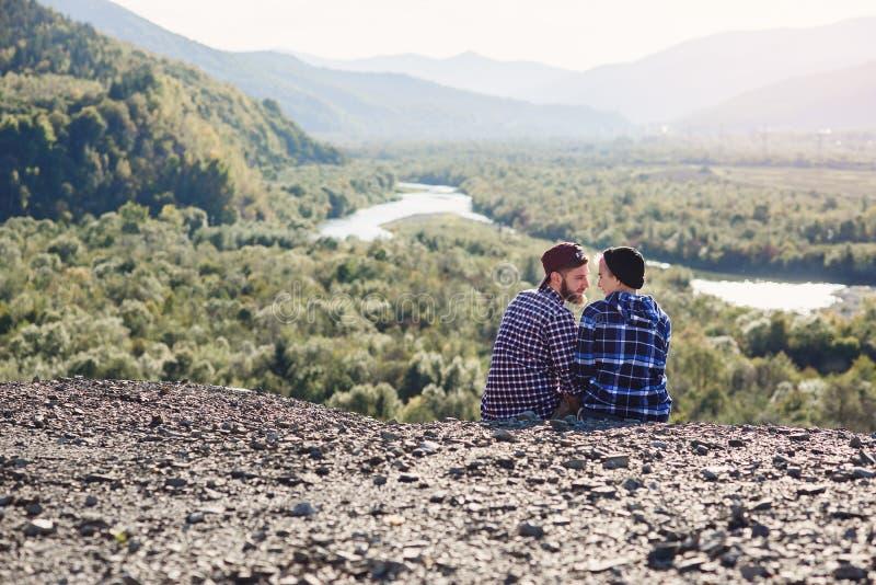 Giovani coppie nell'amore che viaggia insieme in montagne Uomo felice e ragazza dei pantaloni a vita bassa che si siedono insieme fotografie stock