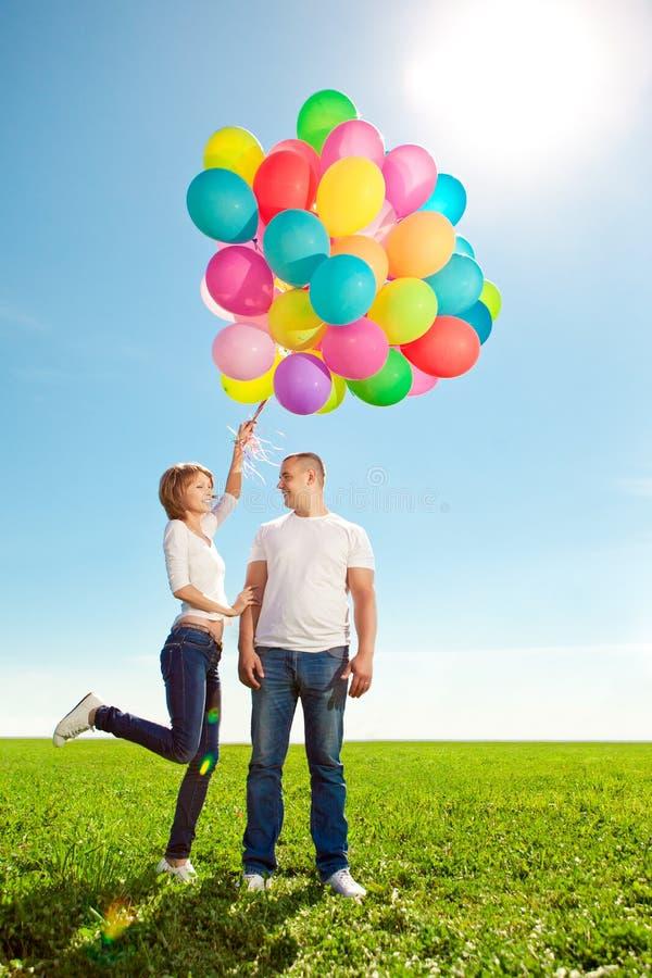 Giovani coppie nell'amore con i palloni in mani nel campo contro immagine stock libera da diritti