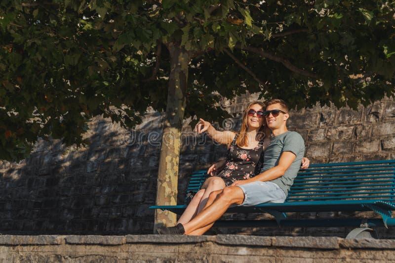 Giovani coppie nell'amore messe su un banco e sul rilassamento durante il giorno soleggiato fotografie stock libere da diritti