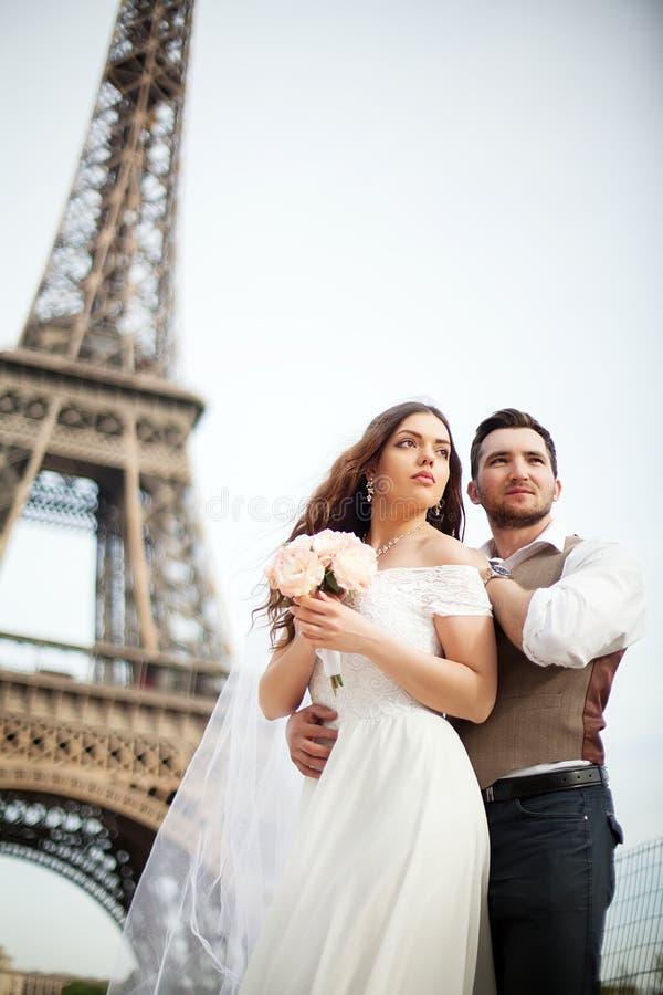 Giovani coppie nell'amore a Parigi sul loro giorno delle nozze immagini stock