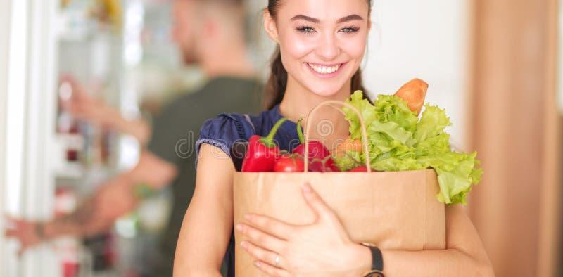 Giovani coppie nella cucina, donna con una borsa di acquisto di drogherie immagine stock