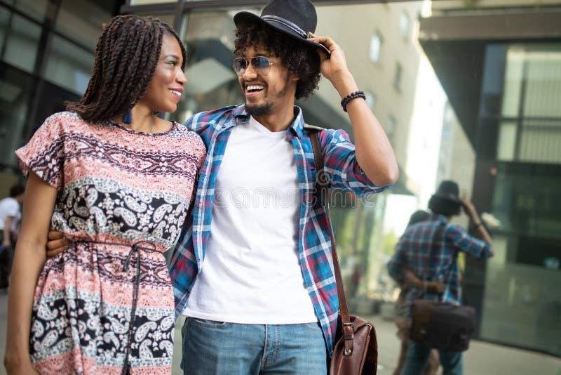 Giovani coppie nere felici che abbracciano e che ridono all'aperto fotografia stock