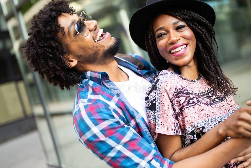 Giovani coppie nere felici che abbracciano e che ridono all'aperto immagini stock libere da diritti
