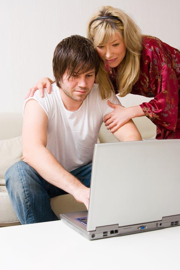 Giovani coppie per mezzo del computer portatile immagini stock