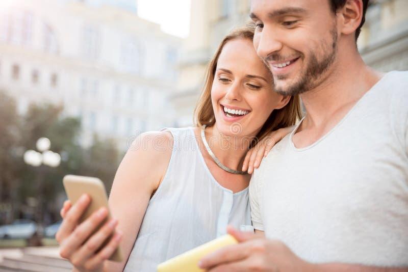 Giovani coppie positive facendo uso dello Smart Phone immagini stock libere da diritti