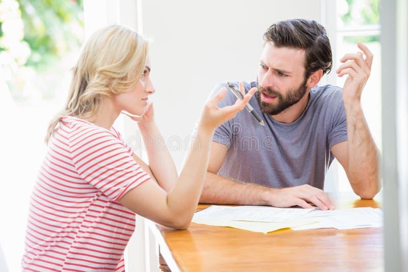 Giovani coppie preoccupate che discutono sulle fatture immagini stock
