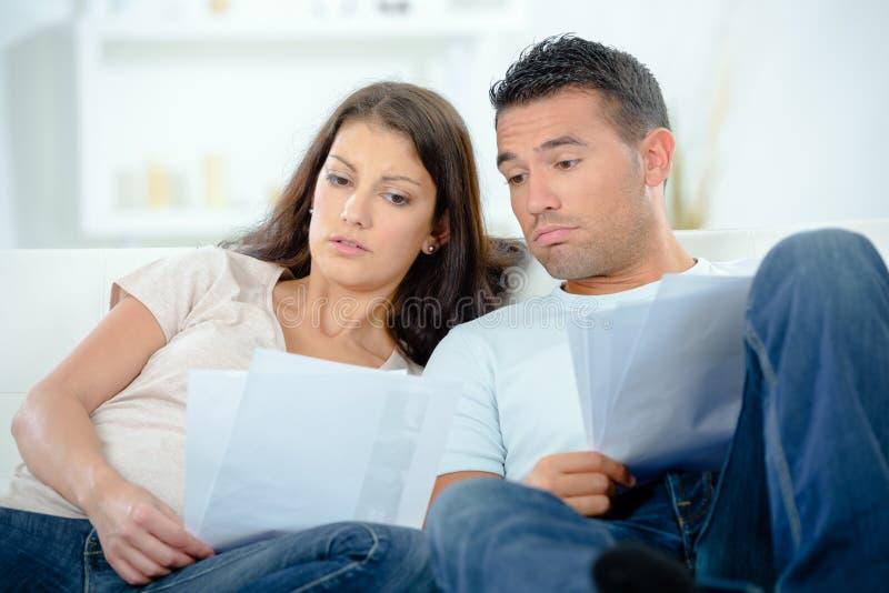 Giovani coppie preoccupate che discutono sulle fatture a casa immagini stock