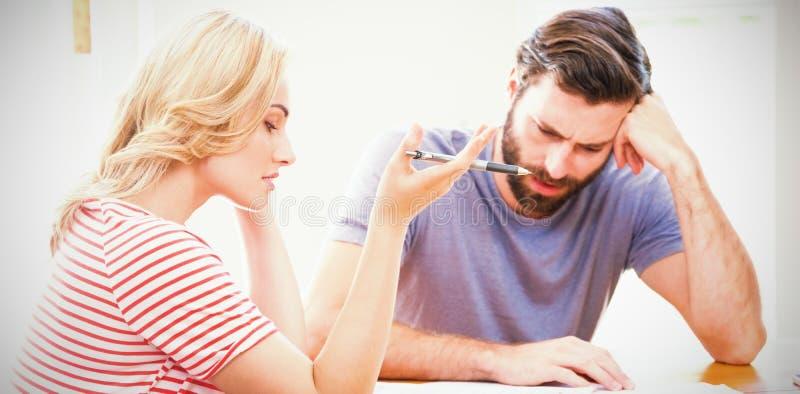 Giovani coppie preoccupate che verificano le fatture fotografia stock