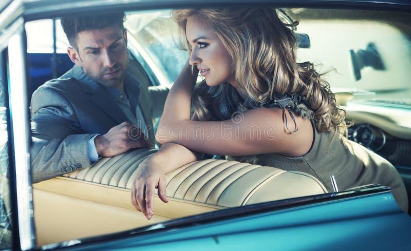 Giovani coppie rilassate nella retro automobile immagine stock