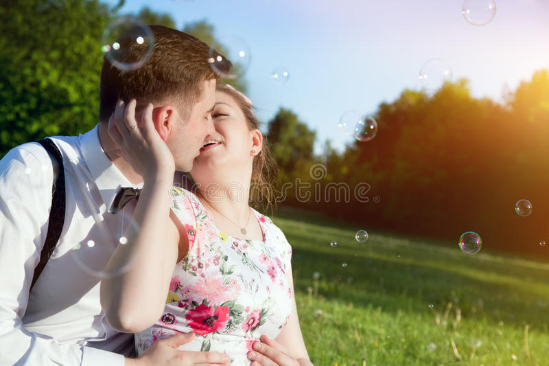 Giovani coppie romantiche che baciano con l'amore nel parco di estate fotografia stock libera da diritti