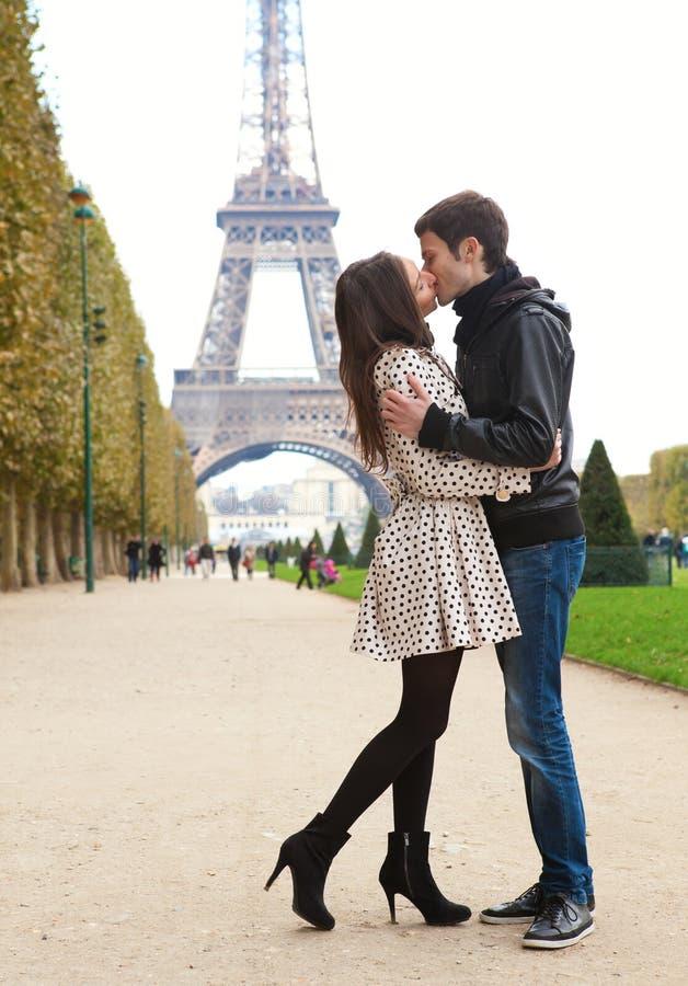 Giovani coppie romantiche che baciano vicino alla Torre Eiffel immagini stock libere da diritti