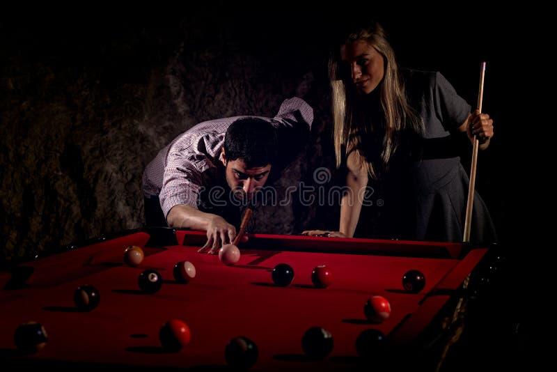 Giovani coppie romantiche che giocano il gioco del biliardo fotografia stock