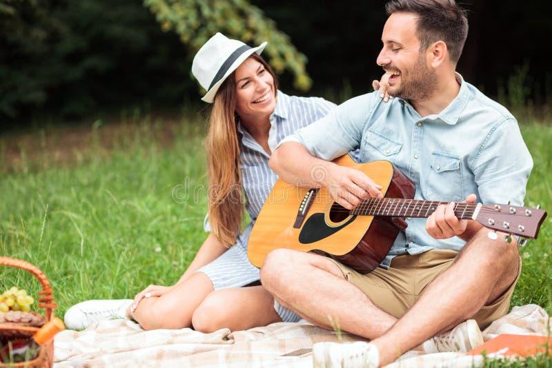Giovani coppie romantiche che si divertono su un picnic, giocanti chitarra e cantanti fotografia stock