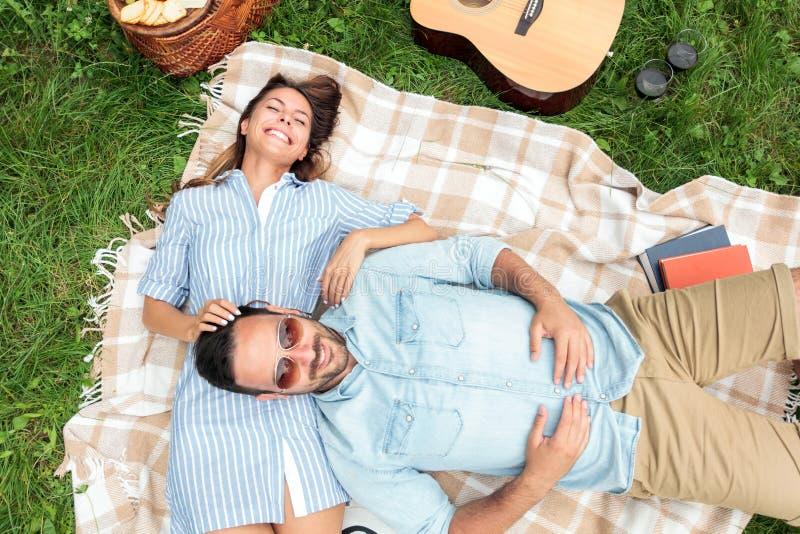 Giovani coppie romantiche che si rilassano in un parco Trovandosi sulle loro parti posteriori su una coperta di picnic, stringent fotografia stock libera da diritti