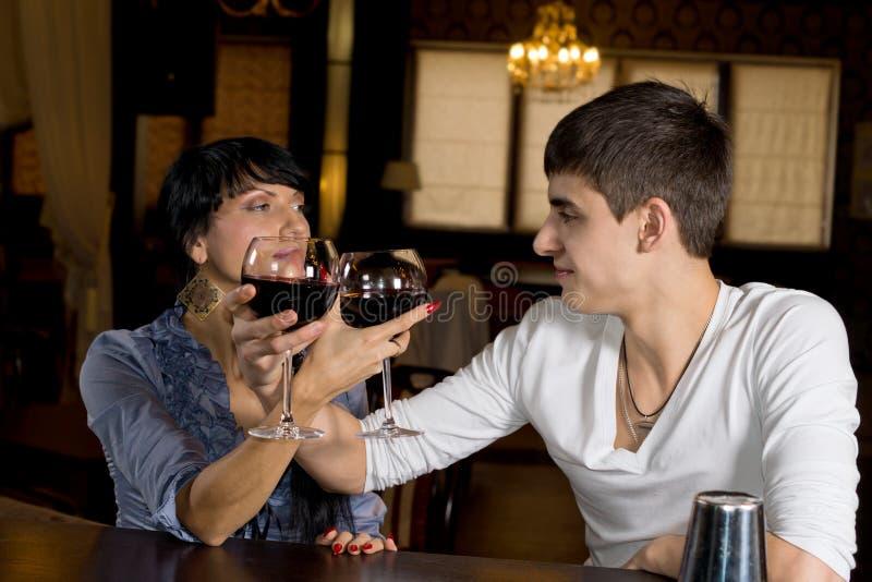 Giovani coppie romantiche che tostano con il vino rosso fotografia stock