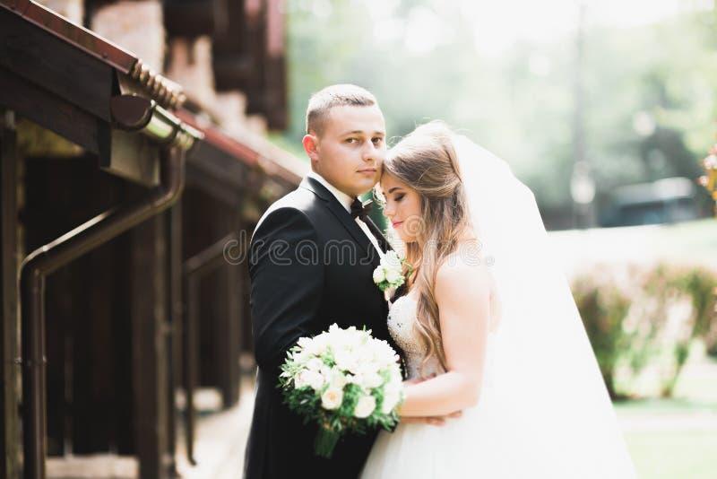 Giovani coppie romantiche felici caucasiche che celebrano il loro matrimonio esterno fotografia stock libera da diritti