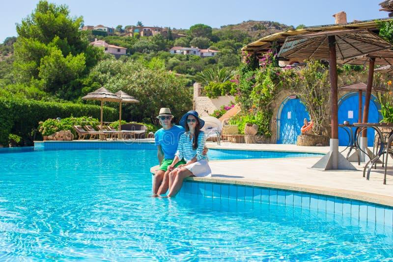 Giovani coppie romantiche felici che si rilassano vicino al nuoto fotografie stock libere da diritti