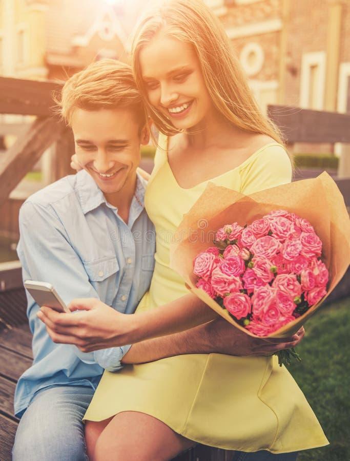 Giovani coppie romantiche nell'amore facendo uso di Smartphone immagine stock