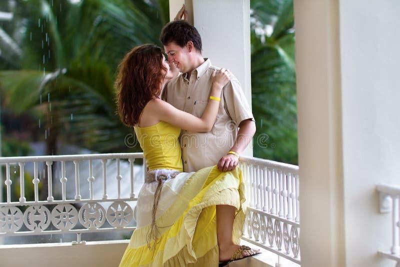Giovani coppie romantiche sul balcone in pioggia tropicale immagine stock libera da diritti