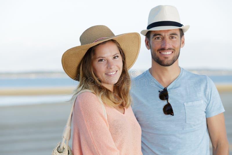 Giovani coppie romantiche sulla riva di mare immagini stock