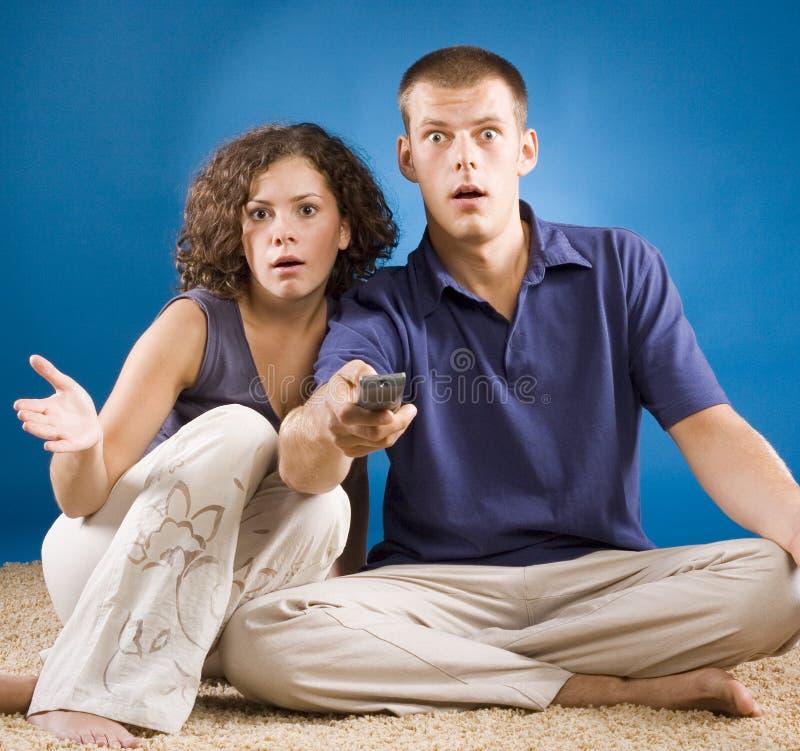 Giovani coppie scosse su moquette con telecomando immagine stock libera da diritti