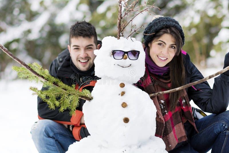 Giovani coppie sorridenti che abbracciano pupazzo di neve immagine stock