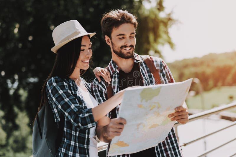 Giovani coppie sorridenti che esaminano aria aperta della mappa immagini stock libere da diritti