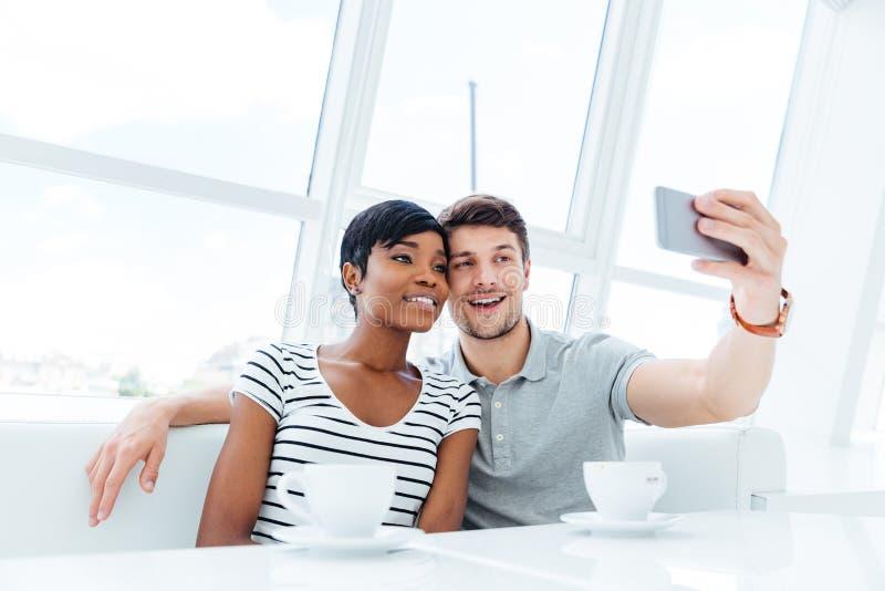 Giovani coppie sorridenti che fanno la foto del selfie sullo smartphone all'interno fotografia stock libera da diritti