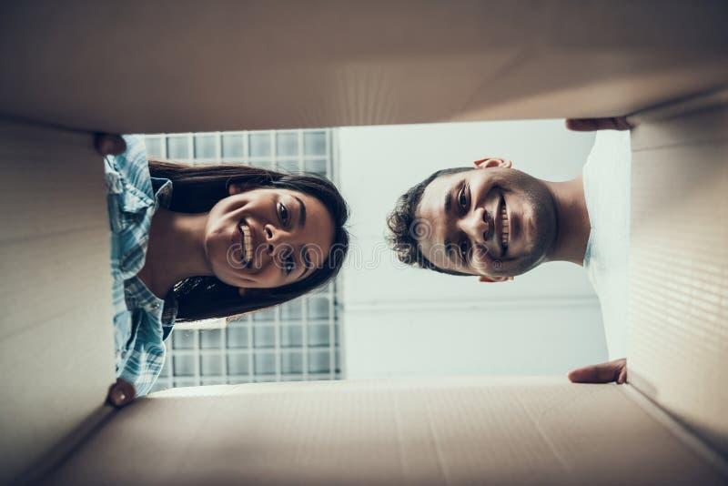 Giovani coppie sorridenti che sembrano la scatola interna di Caton fotografia stock libera da diritti