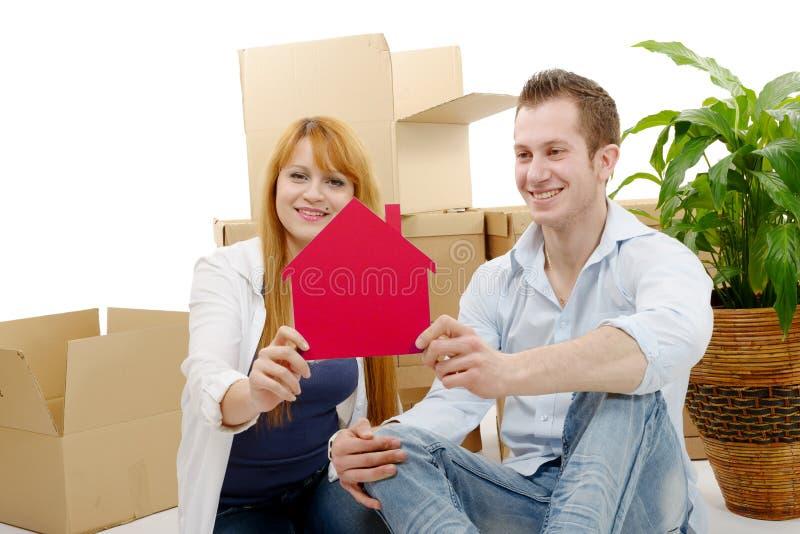 Giovani coppie sorridenti che si siedono dopo la casa commovente fotografia stock libera da diritti