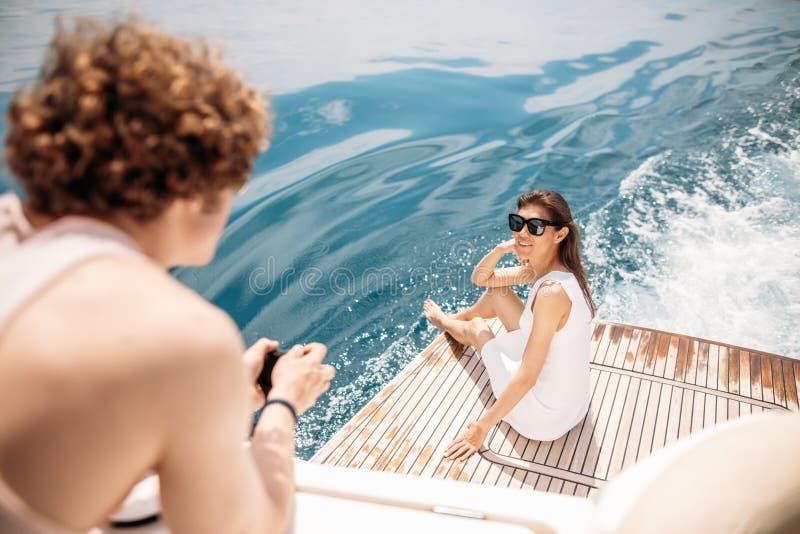 Giovani coppie sorridenti che tengono i vetri con la bevanda mentre viaggiando sull'yacht immagini stock