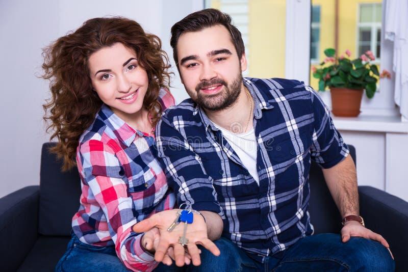 Giovani coppie sorridenti felici che mostrano le chiavi della loro nuova casa fotografie stock