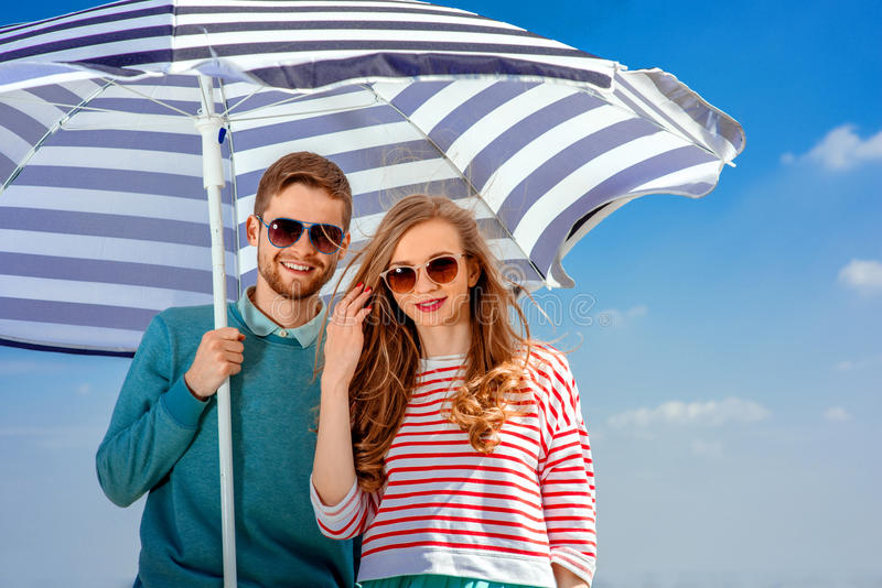 Giovani coppie sorridenti sotto l'ombrello sul fondo del cielo blu fotografie stock