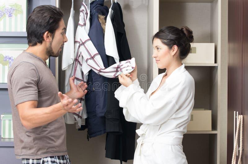 Giovani coppie sposate che scelgono i vestiti in fotografie stock