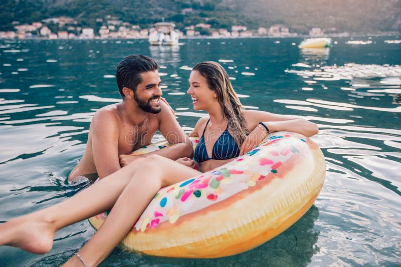 Giovani coppie sul divertiresi della spiaggia fotografia stock
